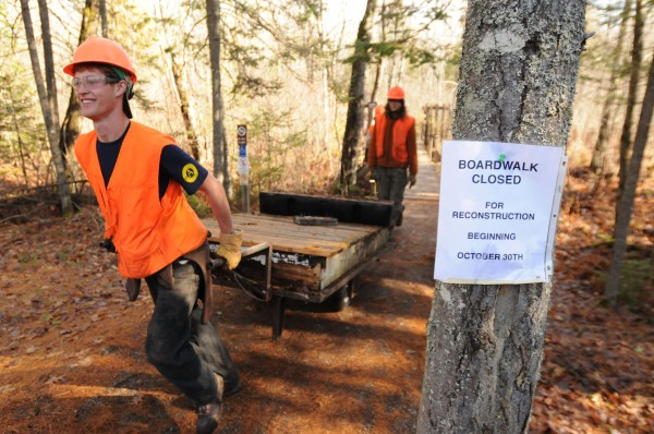 Ethan Harding of Jackson a member of Maine Conservation Corps helps to remove rotten sections of the the Orono Bog Boardwalk Nov. 2.