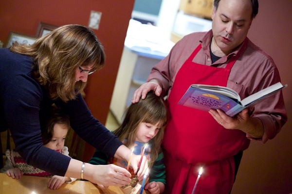 Paula Matlins (from left) helps her daughters Gabrielle, 2, and Hannah, 4, light the menorah while Drew Matlins reads a prayer during the first night of Hanukkah at their home in Bangor. The Matlins spoke about how they're handling the confluence of Hanukkah and Thanksgiving this year as the start of Hanukkah is the day before Thanksgiving.