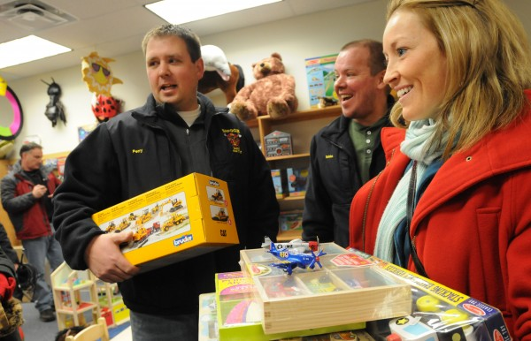 Bangor firefighter Casey Perry, left, and firefighter Scott Bolduc, center, along with Perry's wife Heather stand in line at Robert O. Cupcake's to pay for toys they were purchasing ,with funds they raised, to be donated to Toys for Tots on Saturday night.