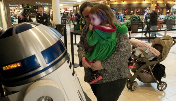 Dustin Lovell of Brewer holds her daughter Leia so she can get a closer look at an R2D2 replica at the Bangor Mall on Saturday. Leia was named after the &quotStar Wars&quot character Princess Leia.