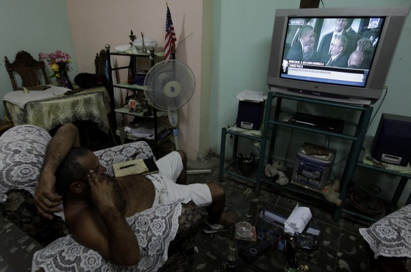A man watches television footage of Cuban President Raul Castro and U.S. President Barack Obama talking during the national memorial service for the late former South African President Nelson Mandela at the First National Bank Stadium, also known as Soccer City, in Havana Dec.10, 2013.