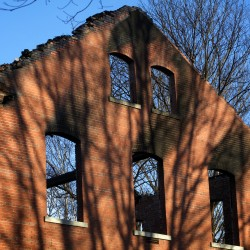Brick walls and chimneys are all that remain after a fire destroyed a hotel under development on Great Diamond Island in Casco Bay.