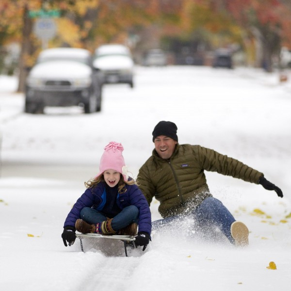 Mark Vogel (right) gives his daughter Parker, 7, a push on the sled on the icy streets in west Fort Worth, Texas, Friday, Dec. 6, 2013.