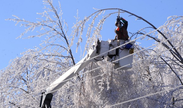 Gardiner-based On Target Utility Services line worker Scott Mitchell cuts down branches that were touching or overhanging the power lines on Valley View Road in Holden, while assisting Bangor Hydro in restoring power to many communities in the area Wednesday, Christmas Day.