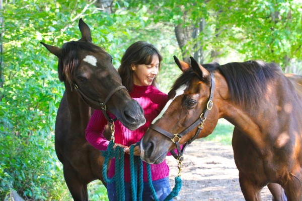 Cassie Astle spends some time with two of her horses, Raffles and Rocket.