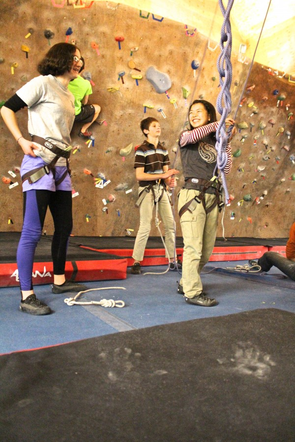 Hannah Rubin, a junior at Bangor High School, talks with exchange student Yuna Shibata of Tokyo, as they both learn to rock climb at Maine Bound Adventure Center during a Bangor High School Outing Club trip on Dec. 10, 2013, at the University of Maine in Orono.