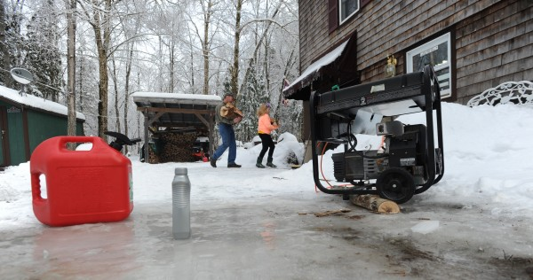Mike and Madi Hussey carry firewood into their home in along Route 1A in Ellsworth on Saturday. The Hussey family has been without power since Monday at noon. They use a gas-powered generator for electricity and a wood stove to keep warm. Hessey said the generator is the same one he bought for the ice storm in 1998.