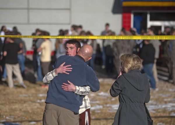 Students gather and reunite with their families at a fast food restaurant across from Arapahoe High School, after a student opened fire in the school in Centennial, Colo., on Friday.