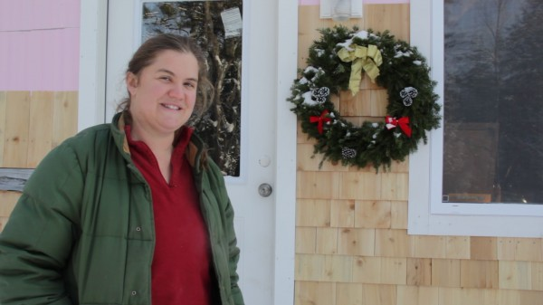 Jennifer Jacques stands outside her nearly completed home, which she and her daughters call the Itty Bitty House. The house used to be an abandoned garage, but, with the help of many, she is converting it into a home. Once she's finished insulating the roof, she will move in.