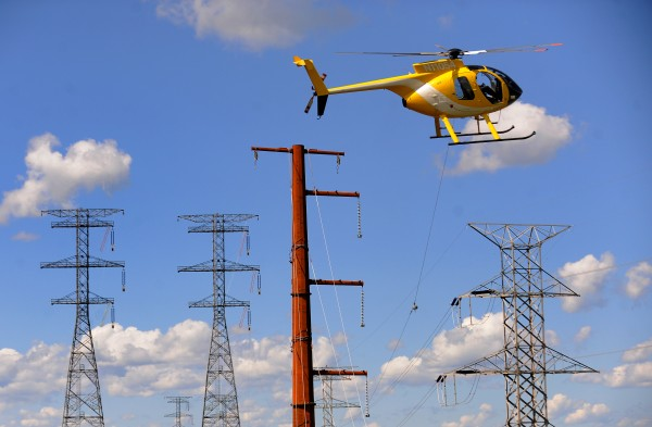 A helicopter pulls the &quotstraw line&quot across the the Penobscot River last year as crews start installing transmission lines to span the 2,419-foot distance between towers in Bucksport and Winterport.
