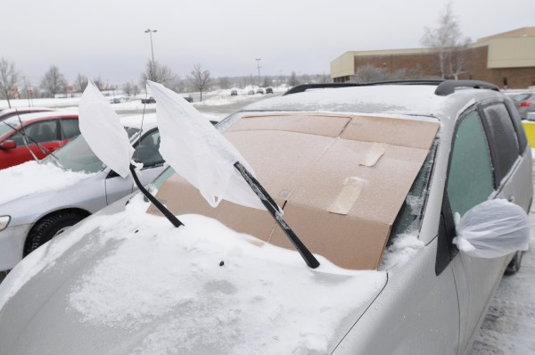 Plastic bags cover both wiper blades and rear view mirrors as cardboard shields the windshield from ice on this car at the Bangor Mall  on Sunday.