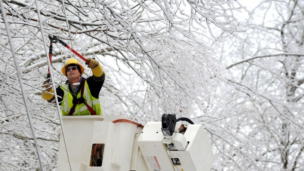 Ken Sivik of Bangor Hydro Electric Co. trims ice covered branches from power lines on Peakes Hill Road in Dedham on Thursday morning. After removing all of the limbs, the line will be energized, restoring power to the area that has been without since Monday.  According to Mike Voisine with Bangor Hydro, crews have been working 16-hour days since Sunday.