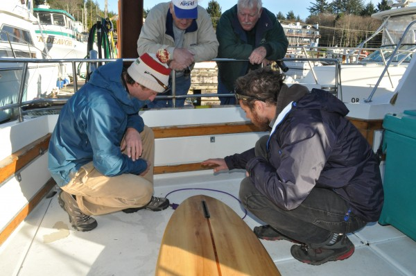 Andrew Gardiner, 25, of Eliot (front left) and Nolan Collins, 26, of York, (front right) show a two Oregon residents the teeth marks on Gardiner's surfboard after being attacked by what they believe was a great white shark on Nov. 22 at Gleneden Beach in Oregon.