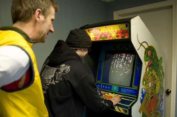Chris Perks watches David Demers play the classic arcade game &quotCentipede.&quot Their Portland Arcade is scheduled to open at the beginning of January on the second floor at 22 Cottage Road in South Portland's Knightville neighborhood.