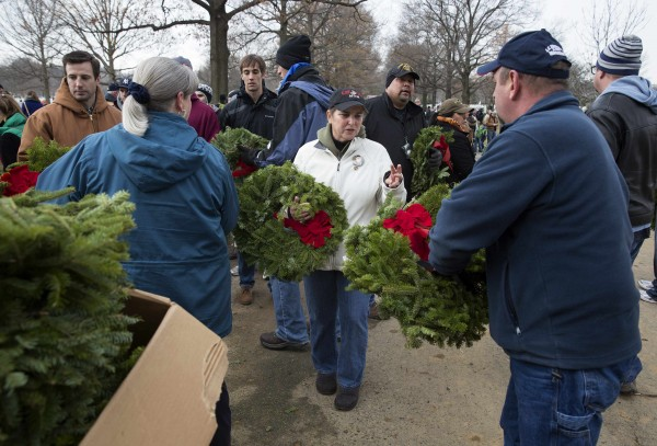 Volunteers and family members of the fallen collect remembrance wreaths before placing them on graves in Section 60 at Arlington National Cemetery in Washington on Saturday.