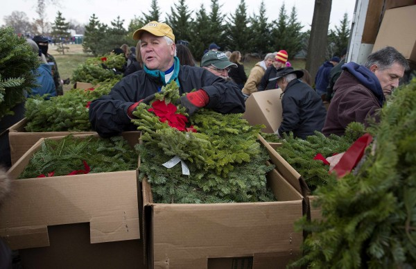 A volunteer distributes remembrance wreaths at Section 60 at Arlington National Cemetery in Washington on Saturday.