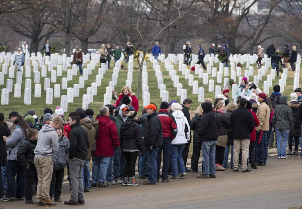 Volunteers await the arrival of remembrance wreaths in Section 60 at Arlington National Cemetery in Washington on Saturday. Volunteers and families of the fallen placed thousands of remembrance wreaths on headstones throughout the cemetery during National Wreaths Across America Day.