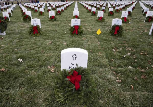 Remembrance wreaths rest in front of graves at Arlington National Cemetery in Washington on Saturday. Volunteers and families of the fallen placed thousands of remembrance wreaths on headstones throughout the cemetery during National Wreaths Across America Day.