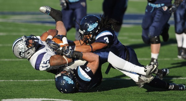 UMaine's Sherrod Baltimore and Troy Eastman bring down UNH's R.J. Harris as he carries the ball against UMaine at Orono during first-half action on Saturday.
