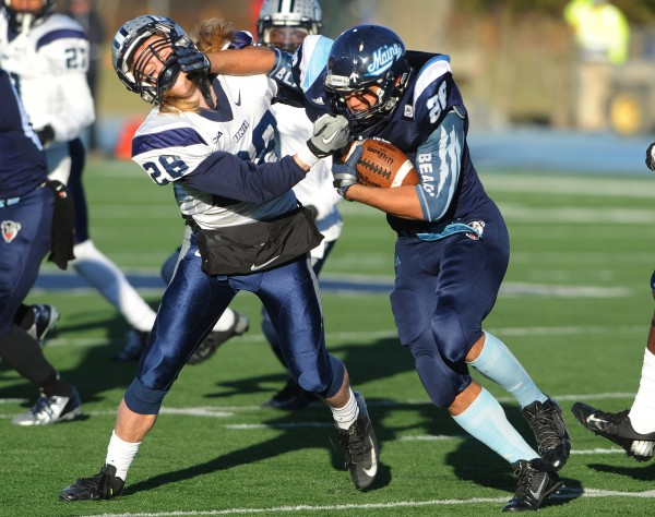 UMaine's Nigel Jones tangles with UNH's Casey DeAndrade as he carries the ball against UNH at Orono during first-half action on Saturday.