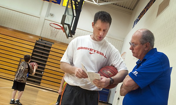 Hermon High School boys basketball coach Mark Reed, center, talks to his father Roger Reed, right, a former longtime Bangor High coach and now a state legislator who assists his son at Hermon. Mark's son practices his skills in the background at Hermon High School Thursday, Dec. 5, 2013.