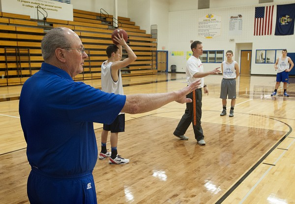Former Bangor High School boys basketball coach Roger Reed, left, works with his son Mark Reed, right,  who is coach of  the Hermon High boys basketball team, during practice at Hermon Thursday, Dec. 5, 2013.