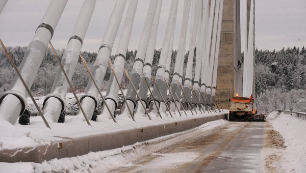 A snowplow clears the Penobscot Narrows Bridge deck of snow and ice debris Monday.