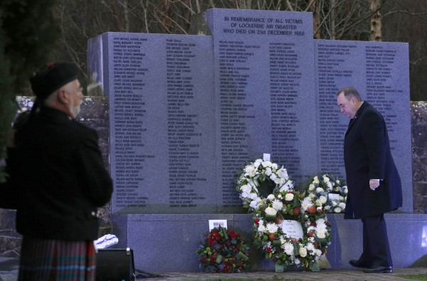 A piper watches as Scotland's First Minister Alex Salmond lays a wreath at a memorial event on the 25th anniversary of the bombing of Pan Am flight 103, in the Dryfesdale Cemetery, in Lockerbie, Scotland, on Saturday.