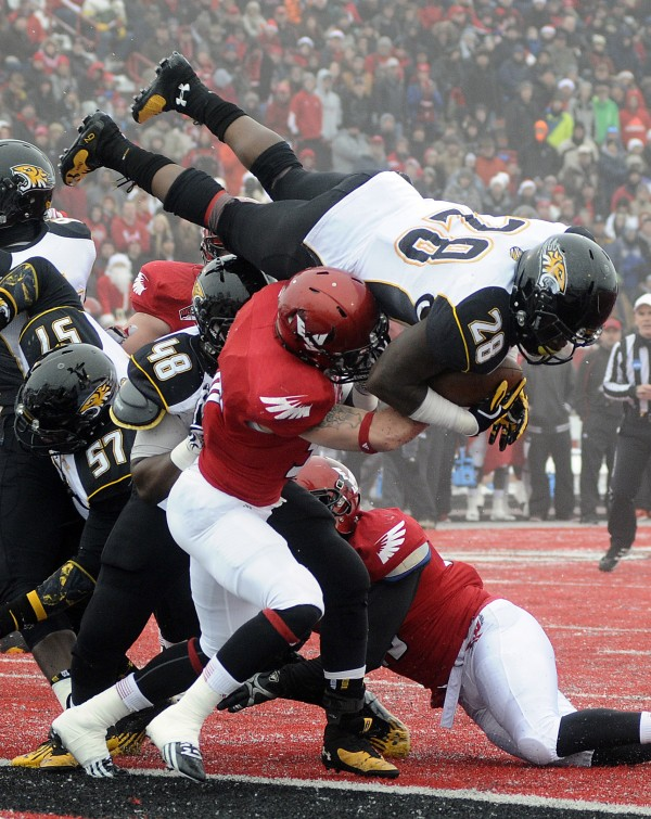 Towson Tigers running back Terrance West (28) leaps for the end zone against Eastern Washington Eagles defensive back Todd Raynes (38) and Cody McCarthy (47) for a touchdown during the first half at Roos Field.