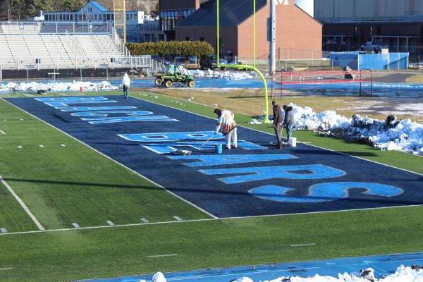 University of Maine staff members prepare Morse Field at Alfond Stadium on Wednesday for Saturday's NCAA football playoff game in Orono against the University of New Hampshire.