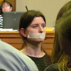 One of three protesters kneels before the audience, back to the City Council, during the Sept. 16 meeting. Two of the demonstrators wore tape over their mouths in part to protest the lack of public input they felt was included in a city deal to sell part of Congress Square park to private developers.