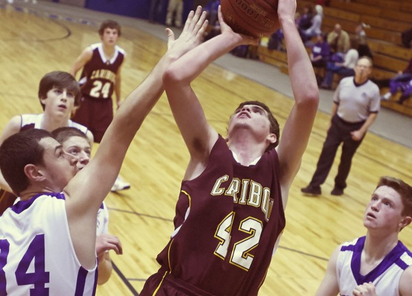 Caribou boy's basketball player Derek Richardson (42) gets his own rebound for another shot past John Bapst' player Andrew Gatchell (34) in the second half of their game at the Bangor Audutorium in Bangor, Saturday, Dec.8, 2012.