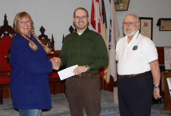 Dixie Shaw, director of Catholic Charities' Feed The County program, accepts a check for $2,000 from Derik Smith and Milt Smith, on behalf of Trinity Lodge 130 in Presque Isle. The funds will be used to feed those in need throughout Aroostook County.