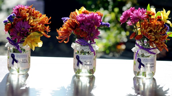 Small bouquets in mason jars lined a table, each with the name of someone who lost his or her life due to domestic violence in Maine this year. There were six bouquets.  Spruce Run Woman Care Alliance held its second annual Walk to End Abuse on Thursday at West Market Square in Bangor.  Purple ribbons were given out at the event.