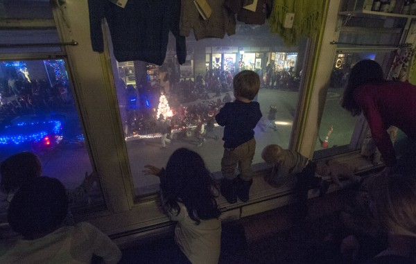 Family and friends of owners Zeth and Betsy Lundy of the Central Street Farmhouse in Bangor watch as the Festival of Lights parade goes by Saturday, Dec. 7, 2013.