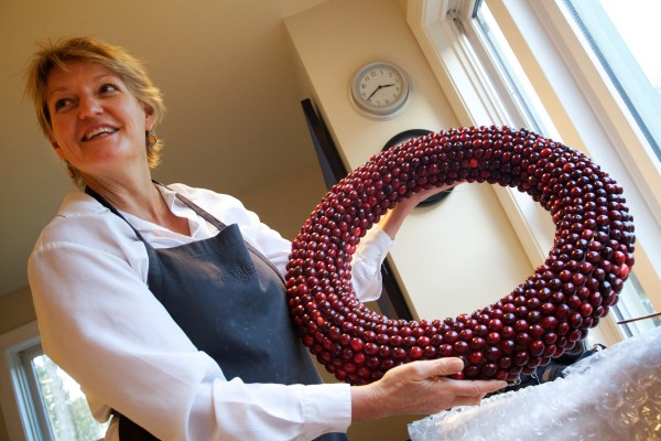 Freeport artist Deena Prestegard holds one of her cranberry wreath creations in her kitchen, where she makes them.