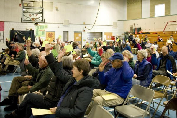 Harpswell voters wave papers to adjourn a special Town Meeting on Saturday, Dec. 7, after approving a nearly $35,000 proposal to extend emergency medical services to around the clock.