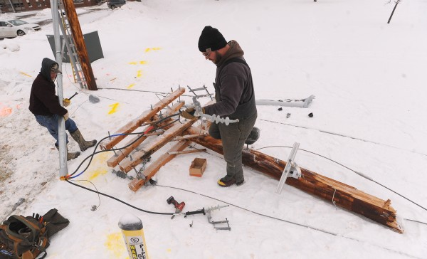 John Parent (left) and Travis Mitchell, electricians with Levant-based Hartt's Electric Service Inc., work on replacing a utility pole on the Eastern Maine Community College campus in Bangor on Thursday afternoon. They said it appears the wires were hanging very low due to the ice and a passing truck caught the wires and snapped the pole.
