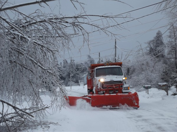Partly framed by bowed trees still heavy with ice, a truck plows snow from a street in a Machias neighborhood Thursday afternoon.