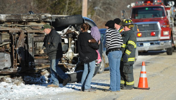 Amanda Sanborn (second from left) holds her daughter Emma Leigh Sanborn as Orrington public works employee Ralph Robshaw, (left) inspects the damage to Sanborn's vehicle on Tuesday along Center Drive in Orrington after Sanborn flipped the SUV.