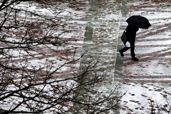A woman crosses Monument Square in Portland Monday as snow turns to cold rain.