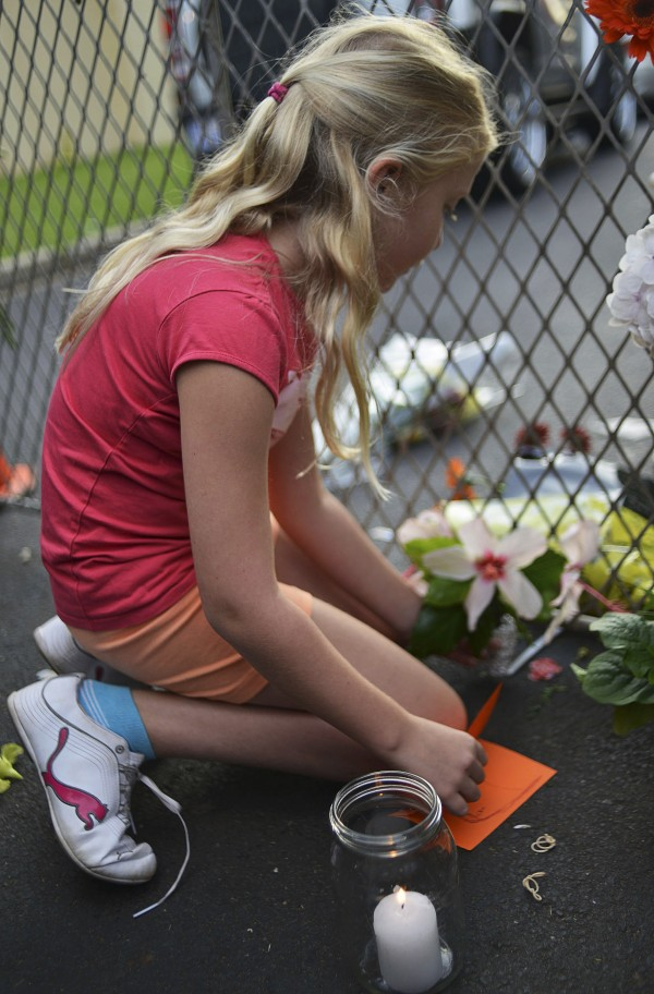 A young girl lights a candle outside the house of former President Nelson Mandela in Johannesburg December 6, 2013.
