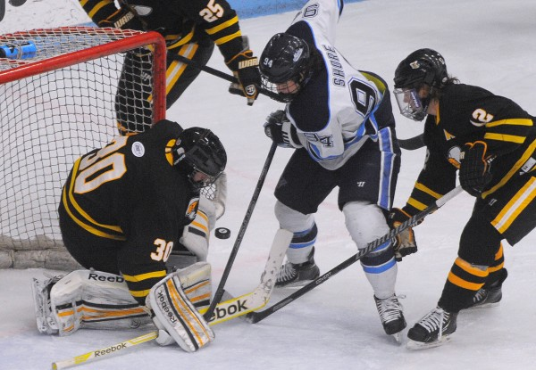 The University of Maine's Devin Shore (center) scrambles for the puck with American International goalie Hunter Leiser (left) and Nick Campanale during the first period Friday night at Alfond Arena in Orono.