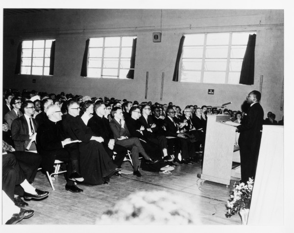 The Rev. Martin Luther King, Jr. speaks before an assembled crowd in a St. Francis College gymnasium, at what is now the University of New England's Biddeford campus, in May of 1964.