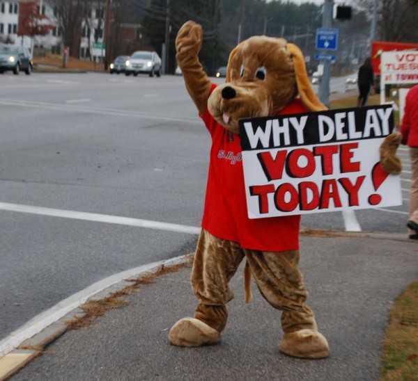 Katy Foley, in a dog costume on U.S. Route 1 outside Scarborough Town Hall, rallies voters Tuesday morning to reject the year-round leash law enacted Oct. 2 by town councilors. Voters repealed the law nearly 3-to-1.