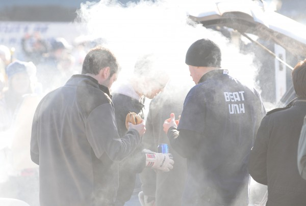 Smoke from a grill engulfs tailgaters at the University of Maine on Saturday as they cook food before UMaine takes on UNH at Orono.