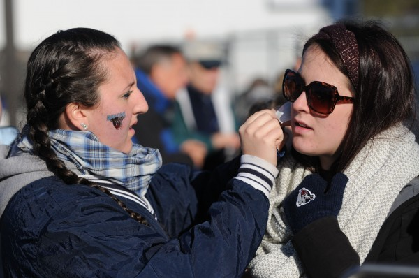Nicole Cosgrove applies a UMaine tattoo to her cousin Carly Cosgrove while tailgating at UMaine before the UMaine UNH game on Saturday in Orono. Carly is head football coach Jack Cosgrove's daughter.