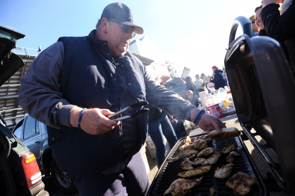 Billy Perillo of Willmington Del., father of Maine tight end Justin Perillo, mans the grill during tailgating festivities in the parking lot of the University of Maine on Saturday in Orono.
