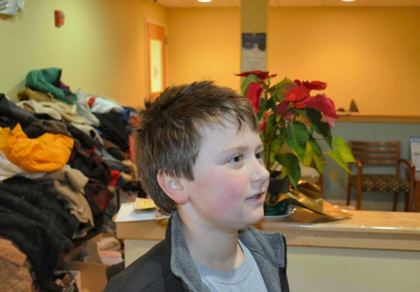 Evan Vigue, 9, of Waterville donated $65.43 to the Mid-Maine Homeless Shelter in Waterville on Monday during a cash mob hosted by Mayor Karen Heck.