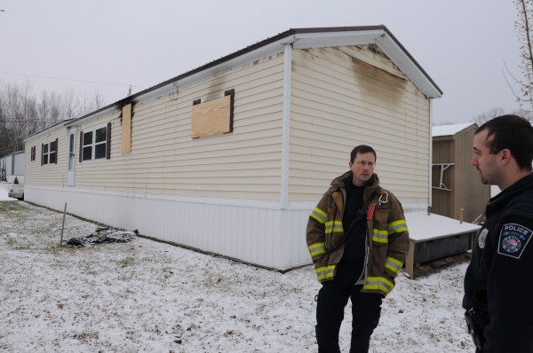 Fire Capt. Pete Metcalf (left) and Patrolman Matthew Parkhurst stand beside the mobile home on Chase Road on Sunday that was the scene of a rescue that tested the quick response and teamwork of the first responders, who saved a man's life.